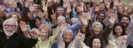 Stock Photo of Large group of multi-ethnic people cheering with arms raised