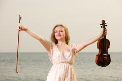 happy blonde girl with a violin outdoor - stock photo