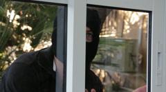 Burglar entering through a sliding window Stock Footage