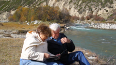 Happy elderly couple sitting on the bank of the river and watch the photo album Stock Footage