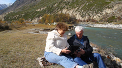 Happy elderly couple sitting on the bank of the river and watch the photo album - stock footage