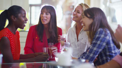 Happy group of female friends gossiping over drinks Stock Footage
