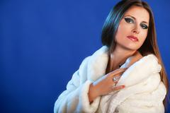 woman in fur on blue background winter style diamond ring and luxury jeweller - stock photo