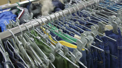 Clothing hanging on hangers at clothes shop Stock Footage