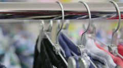 Stock Video Footage of Dolly: Clothes on Hangers at Clothing Store