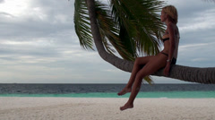 Beautiful girl sitting on the bent down coconut palm by the sea. Maldives. Stock Footage