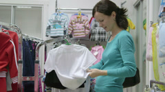 Woman shopping in clothes shop Stock Footage