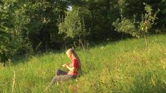 Woman girl sms text message text send nature park grass sitting blonde summer Stock Footage