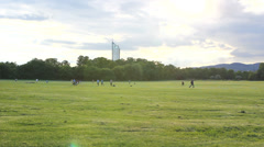 People play and walk ongreen large lawn, modern building in background Stock Footage