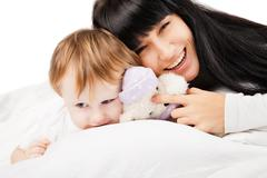 Stock Photo of happy family. Mother with baby playing and smiling