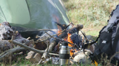 Backpack by campfire at the camp site Stock Footage