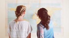 Tourist girls looking at world map planning travel adventure Stock Footage