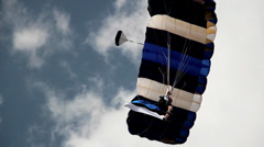 Guy on parachute lands Stock Footage