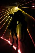 Silhouette of Girls Dancing in Nightclub in front of Lasers - stock photo