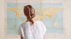 Tourist woman looking at world map planning travel adventure Stock Footage