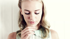 Pretty girl drinking milk with straw Stock Footage