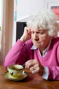 depressed elderly woman sitting at the table - stock photo