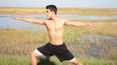 Young man doing yoga. Peaceful environment. Outdoors Stock Footage