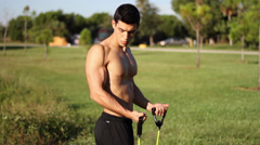 Muscular young man doing arm exercises with a resistance band Stock Footage
