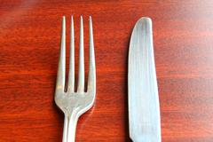 fork and spoon isolated on dining table - stock photo