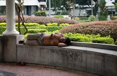 homeless men sleeping in a park - stock photo