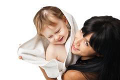 Mother with her baby after bathing in white towel - stock photo