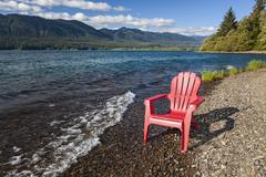 Adirondack chair by lake Stock Photos