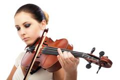 Beautiful young woman playing violin over white - stock photo