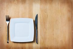empty plate with fork and knife on wooden table, table arrangement - stock photo