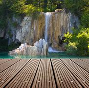 Waterfall and empty wooden deck table. ready for product montage display. Stock Photos