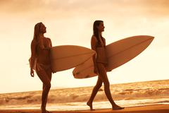 Stock Photo of surfer girls on the beach at sunset in hawaii