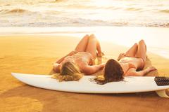 Surfer girls on the beach at sunset in hawaii Stock Photos
