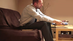 Tired businessman after work relaxing in front of tv in home HD Stock Footage