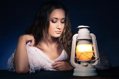 Beautiful woman sitting with lantern over dark Stock Photos