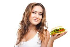 Stock Photo of Happy Young Woman Eating big yummy Burger isolated