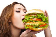 Happy Young Woman Eating big yummy Burger isolated - stock photo