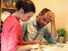 Sad couple reading newspaper ads in home NTSC - stock footage