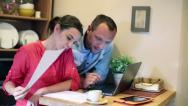 Stock Video Footage of Happy couple calculating their bills on laptop by the table at home HD