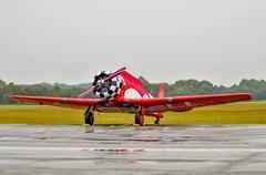 red aerobatics plane parked due to rain - stock photo