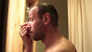 Stock Video Footage of Handsome man applying concealer on his eyelid in bathroom HD