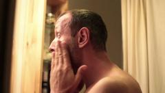Handsome man applying moisturiser creme on his face in bathroom HD Stock Footage