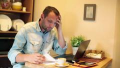 Sad, overwhelmed man calculating bills by the table at home HD Stock Footage