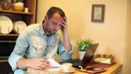 Stock Video Footage of Sad, overwhelmed man calculating bills by the table at home HD