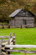 beautiful autumn scene showing rustic old log cabin surrounded by split rail  - stock photo
