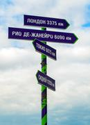 Signpost with many arrows pointing on sky - stock photo