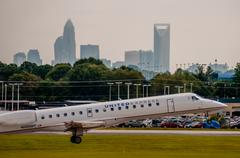 Commercial jet on an airport runway with city skyline in the background. Stock Photos