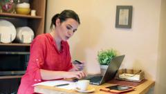 Woman paying bills online on laptop by the table at home HD Stock Footage