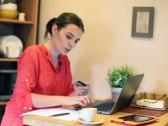 Stock Video Footage of Woman paying bills online on laptop by the table at home NTSC