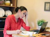 Stock Video Footage of Sad, overwhelmed woman with bills by the table at home NTSC