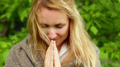 Blonde woman holds her hand together in namaste sign and prays Stock Footage